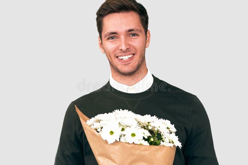 Portret szczęśliwy przystojny mężczyzna ono uśmiecha się dawać bukietowi biali kwiaty zdjęcie royalty free