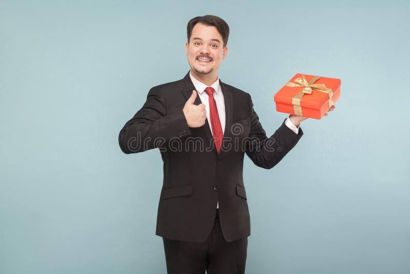 Portret szczęście biznesowego mężczyzna mienia prezenta pudełko, seansu lik zdjęcie royalty free