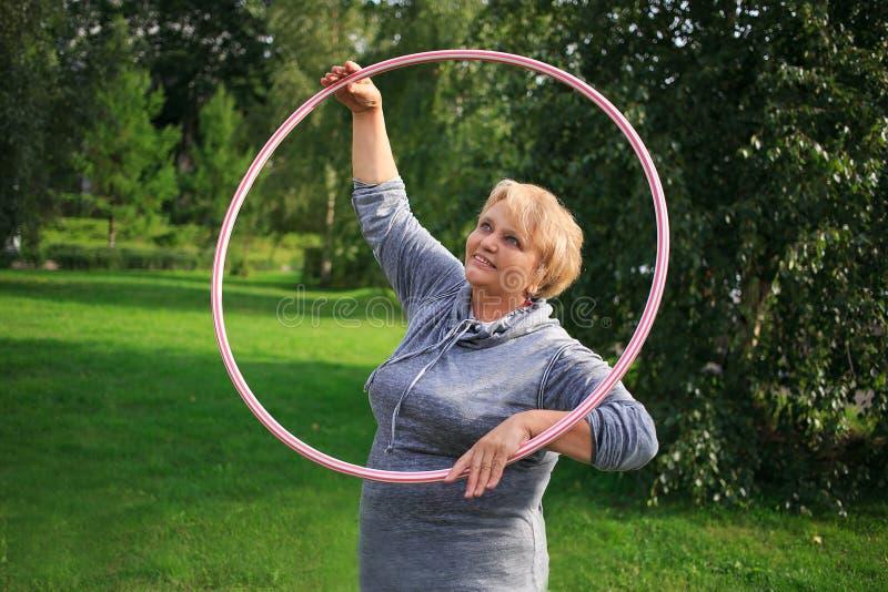 Portret szczęśliwa ładna starsza kobieta ćwiczy z kolorowym hula obręczem na natury tle zdjęcie royalty free