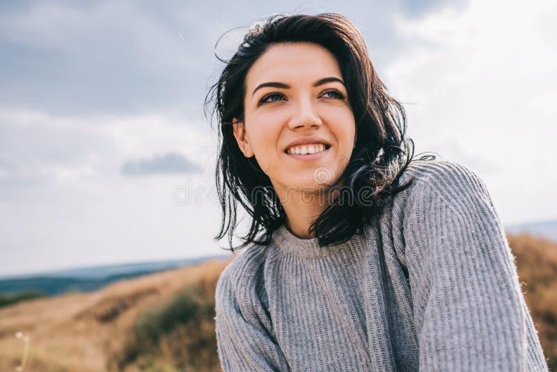 Portret szczęśliwa, śmieszna brunetki kobieta i, przeciw natury łące i chmurzącemu tłu z wietrznym włosy obrazy stock