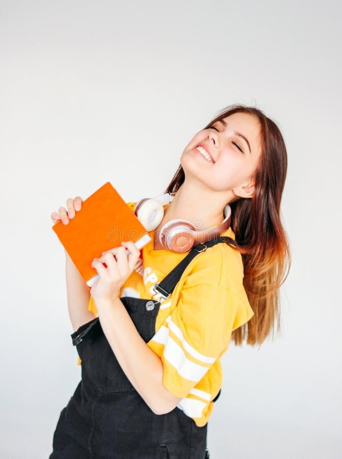 Portret szczęśliwa beztroska uśmiechnięta nastolatek dziewczyna z ciemny długie włosy w żółtej koszulce z copybook na popielatym  obraz stock