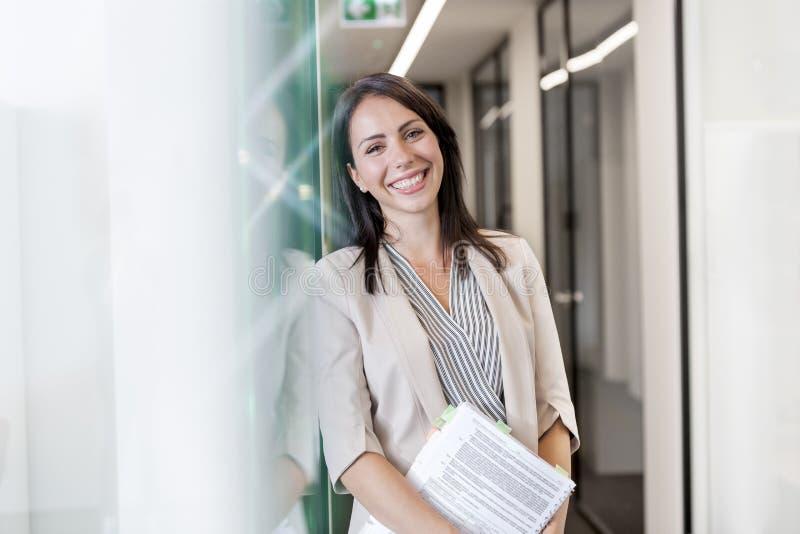 Portret szczęśliwa bizneswoman pozycja z dokumentami ścianą przy biurem fotografia stock