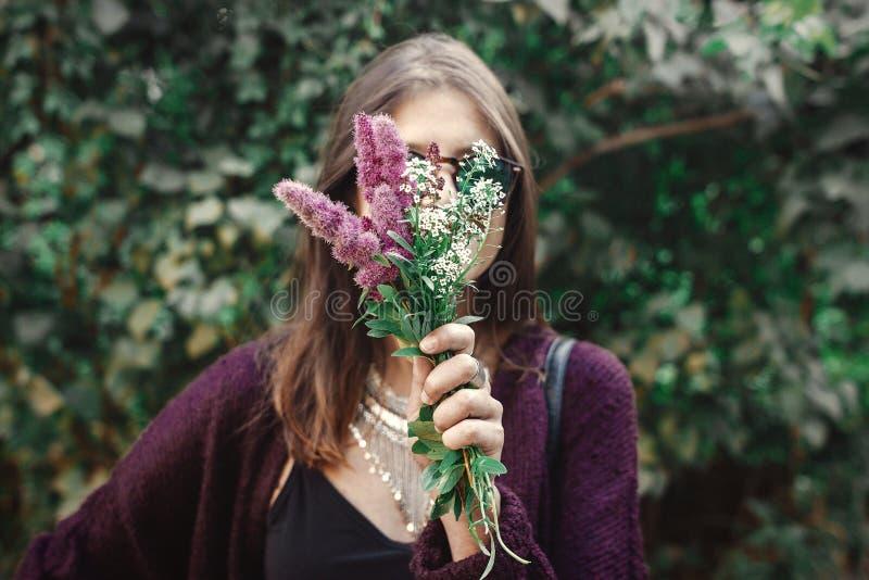 Portret szczęśliwa boho dziewczyna ono uśmiecha się z bukietem wildflowers w pogodnym ogródzie w okularach przeciwsłonecznych Ele fotografia royalty free