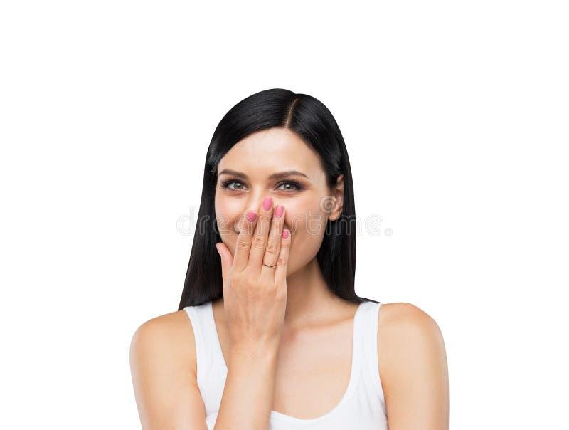 Portret szczęśliwa brunetki dama w białym podkoszulku bez rękawów który zakrywa jej usta ręką fotografia stock