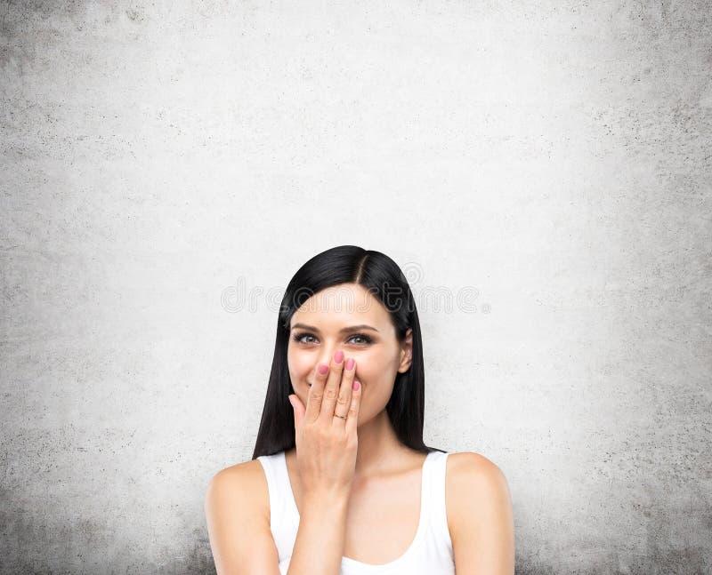 Portret szczęśliwa dama w białym podkoszulku bez rękawów który zakrywa jej usta ręką Betonowy tło fotografia royalty free