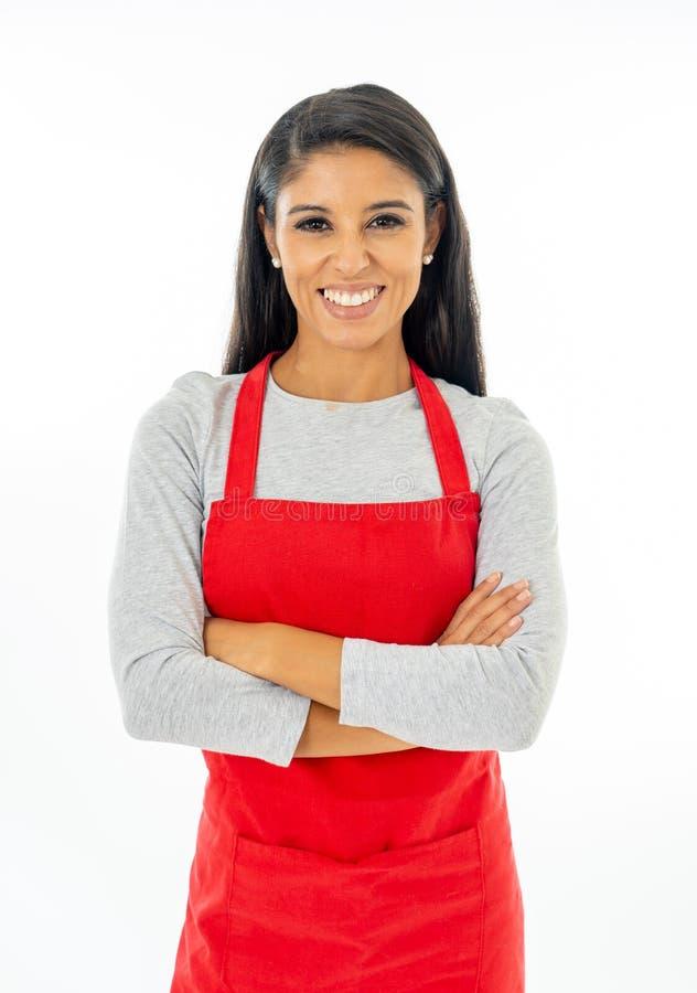 Portret szczęśliwa dumna piękna łacińska kobieta jest ubranym czerwonego fartucha uczenie gotować robić kciukowi up gestykuluje w fotografia royalty free