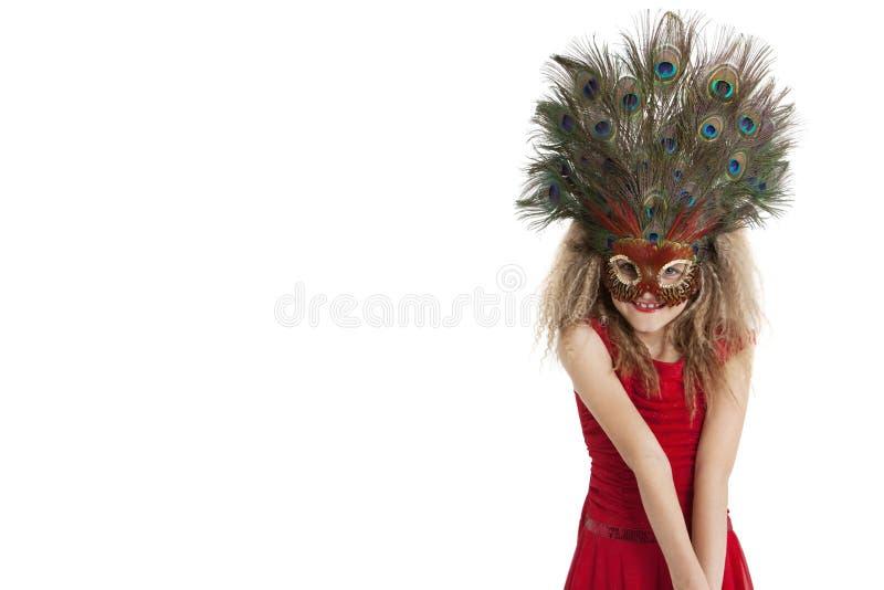 Portret szczęśliwa dziewczyna jest ubranym pawia piórka maskę nad białym tłem obraz stock