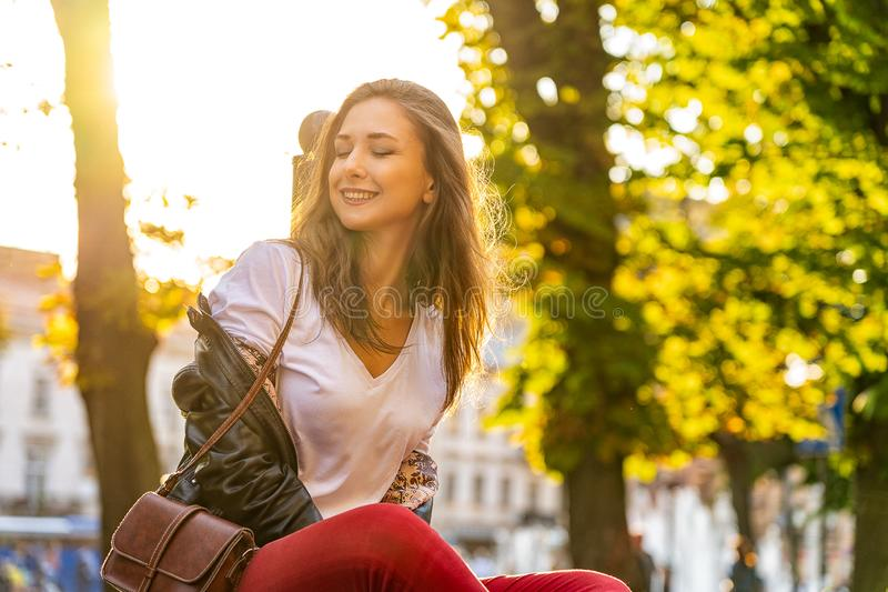 Portret szczęśliwa dziewczyna siedzi w słońcu, mruga ona z backlight, oczy i ono uśmiecha się outdoors fotografia royalty free