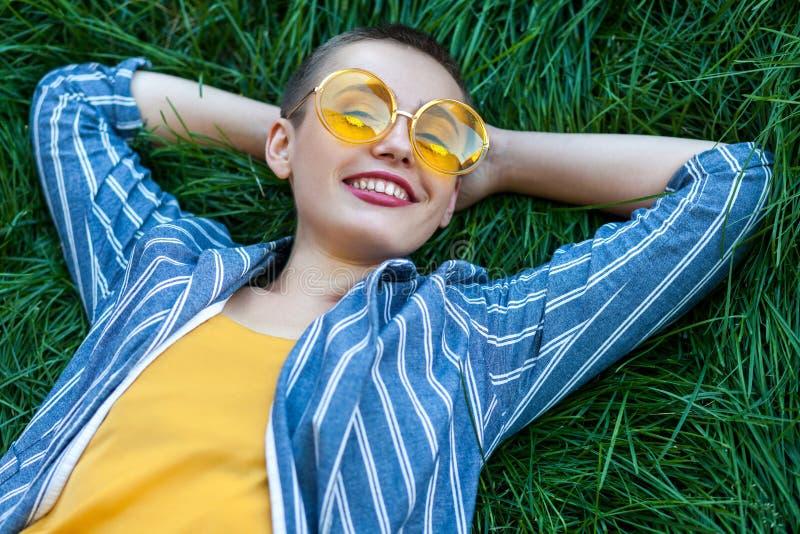 Portret Szczęśliwa galanteryjna młoda kobieta z krótkim włosy w przypadkowym błękicie paskował kostium, żółta koszula, obrazy stock