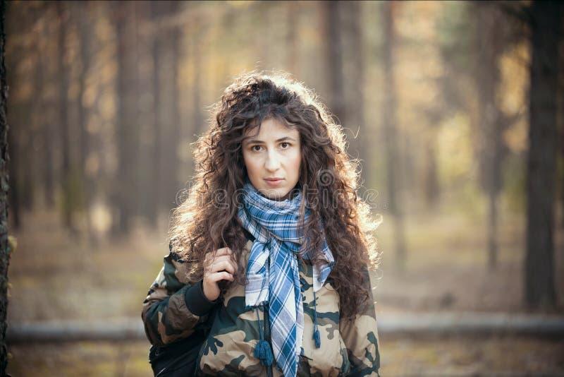 Portret szczęśliwa kobieta z kędzierzawym włosy w jesieni Radosna młoda kobieta ma zabawę w pogodnym spadku parku obraz royalty free