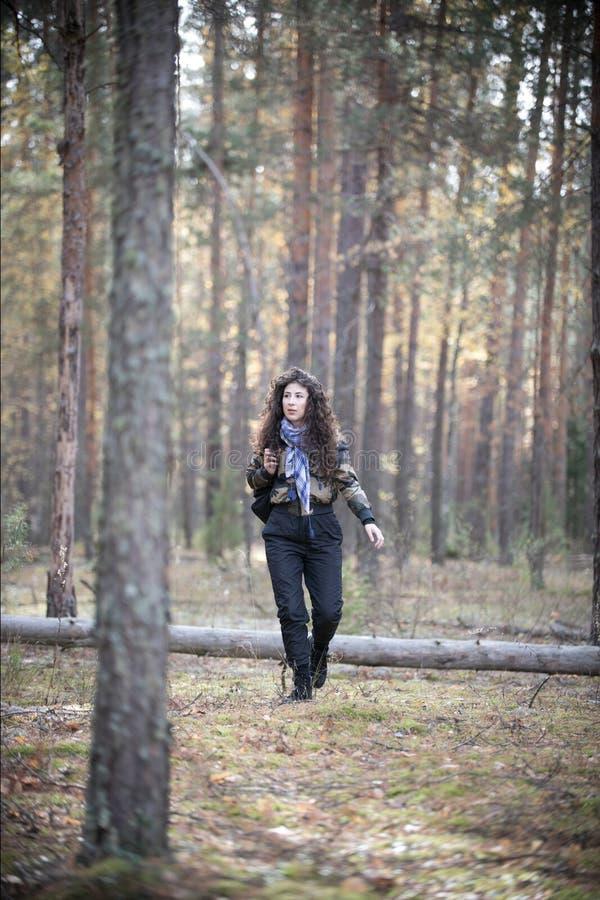 Portret szczęśliwa kobieta z kędzierzawym włosy walkin wśród drzew w jesieni Radosna i uśmiechy młoda kobieta ma zabawę w fotografia stock