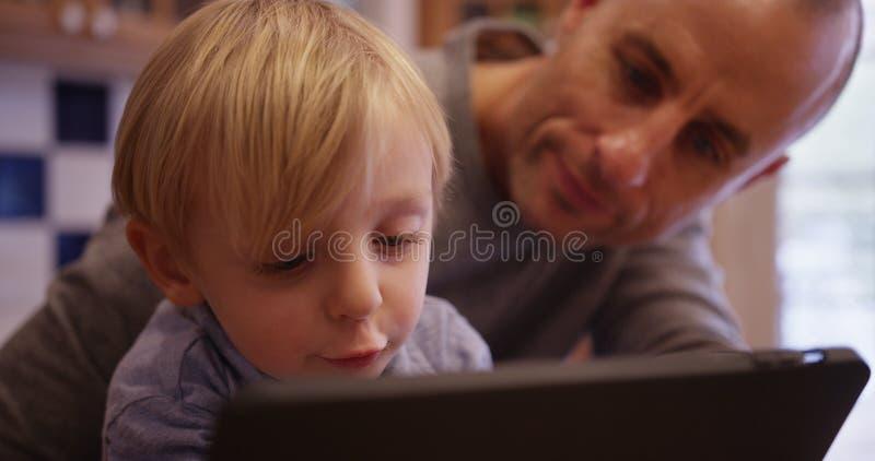 Portret szczęśliwa młoda chłopiec czyta ebook z jego ojcem fotografia stock
