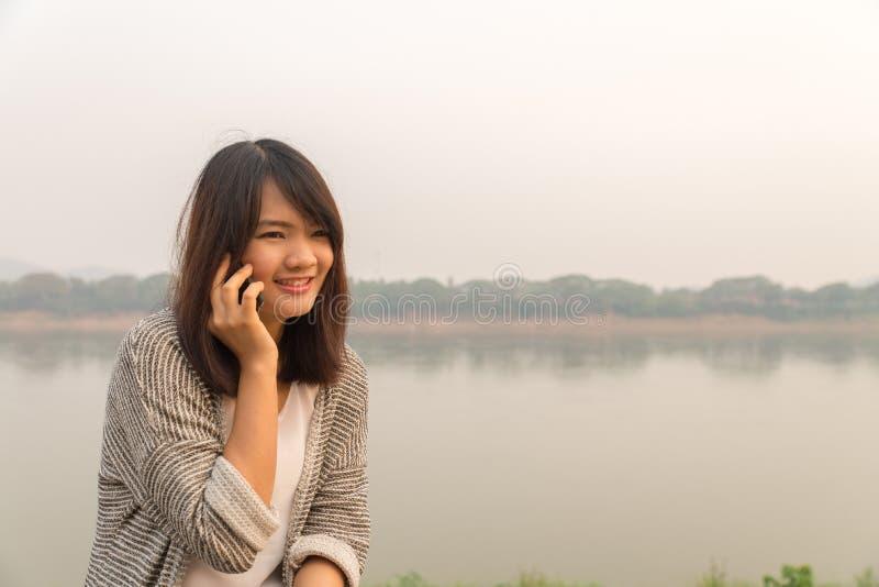 Portret szczęśliwa młoda kobieta ono uśmiecha się i chodzi w ulicie używać opowiadać na smartphone i patrzeć kamerę obraz stock