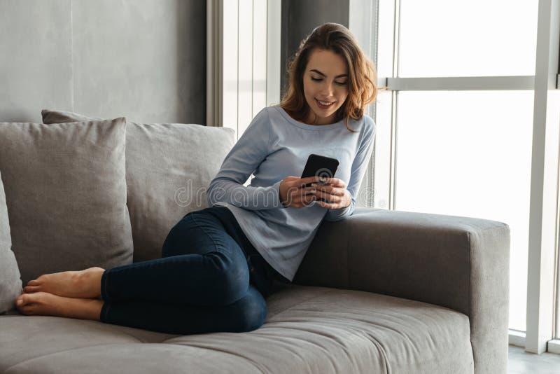 Portret szczęśliwa młoda kobieta używa telefon komórkowego obraz stock