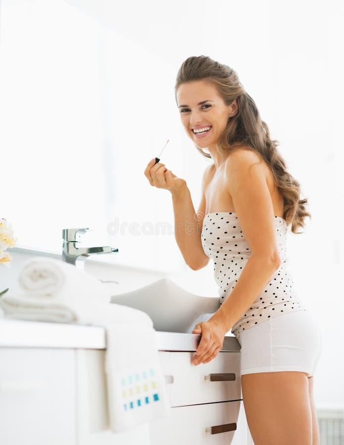 Portret szczęśliwa młoda kobieta z wargi glosą w łazience zdjęcie royalty free