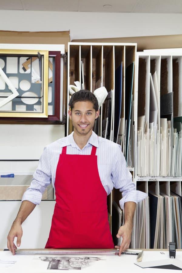 Portret szczęśliwa młoda wykwalifikowany robotnik pozycja z metrowym kijem w warsztacie fotografia stock