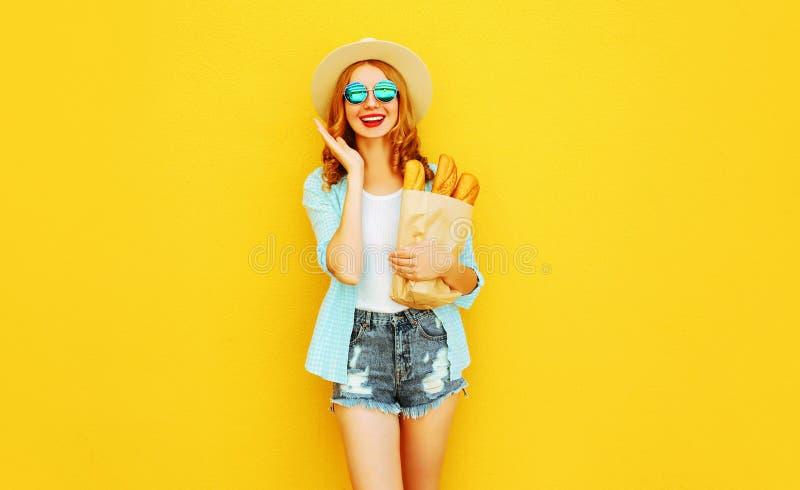 portret szczęśliwa ono uśmiecha się zdziwiona kobieta trzyma papierową torbę z długim białego chleba baguette, jest ubranym słomi zdjęcia stock
