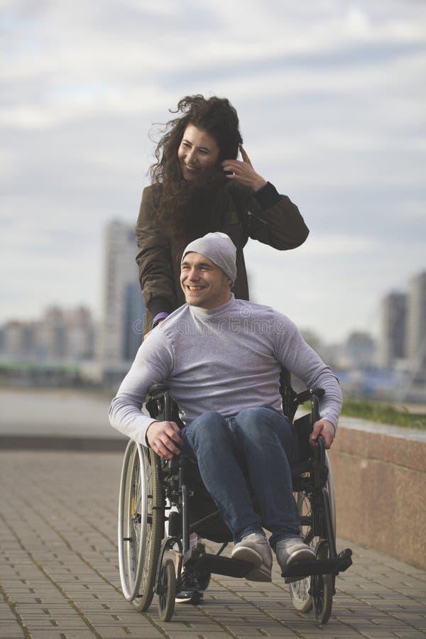 Portret szczęśliwa para - dbać kobiety z niepełnosprawnym mężczyzna w wózku inwalidzkim obraz stock