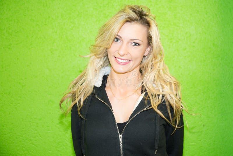 Portret szczęśliwa piękna blond dziewczyny kobieta jest ubranym przypadkowych ubrania w zielonym tle obraz stock