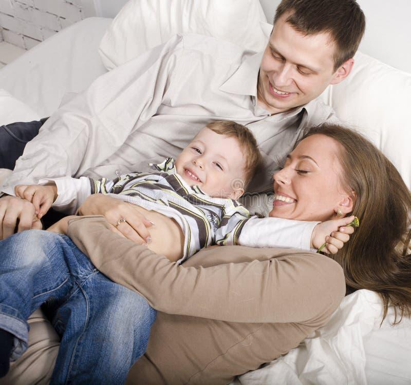 Portret szczęśliwa rodzina, mama i tata bawić się z ich synem w łóżku, obrazy stock