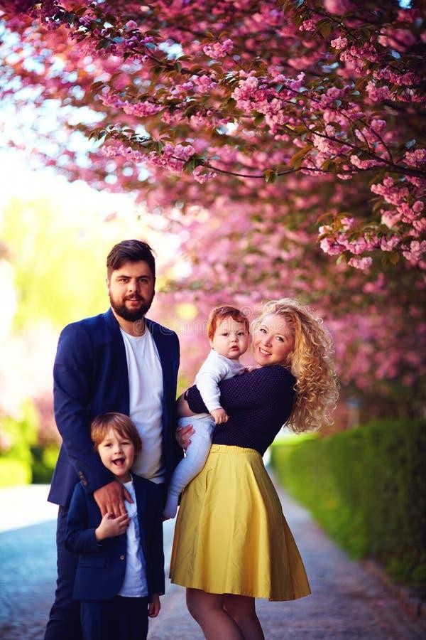 Portret szczęśliwa rodzina na spacerze wzdłuż kwitnącej wiosny ulicy zdjęcia royalty free