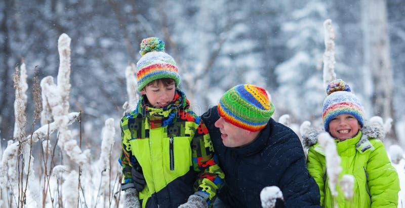 Portret szczęśliwa rodzina w zima parku Ojciec, syn i mały córki śmiać się, obrazy stock