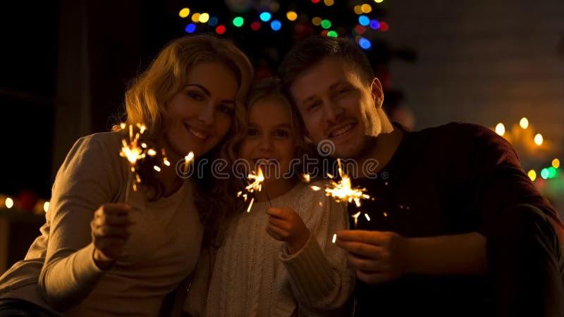 Portret szczęśliwa rodzina z Bengal światłami, świętuje boże narodzenia wpólnie zdjęcie stock