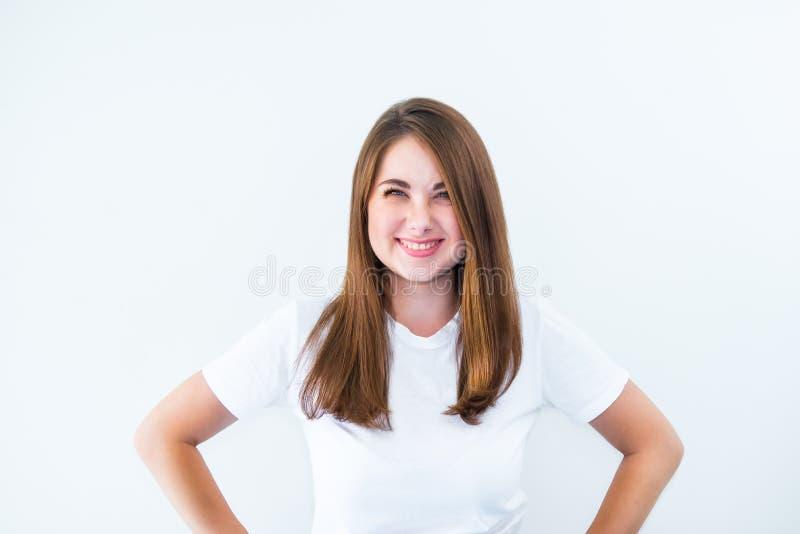 Portret szczęśliwa roześmiana dziewczyna z zezowaniem przygląda się flirtować przy kamerą odizolowywającą na białym tle Potomstwa zdjęcia royalty free