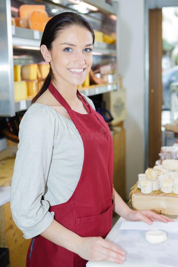 Portret szczęśliwa sprzedawczyni w sera sklepie zdjęcia stock