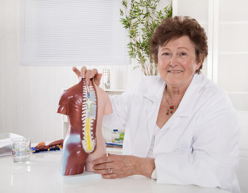 Portret szczęśliwa stara senior lekarka wyjaśnia ciała ludzkiego zdjęcie royalty free