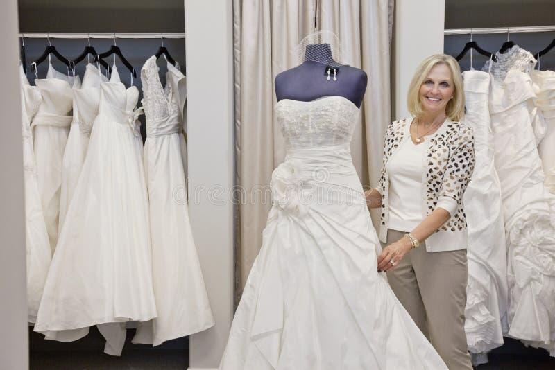 Portret szczęśliwa starsza kobieta przystosowywa ślubną suknię na mannequin w bridal sklepie obrazy stock