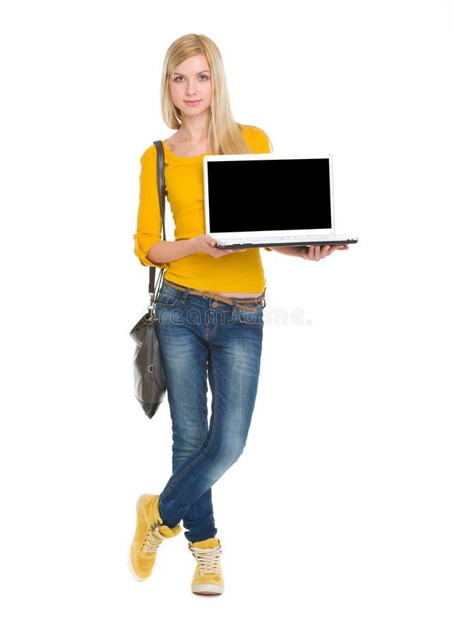 Portret szczęśliwa studencka dziewczyna pokazuje laptop fotografia stock