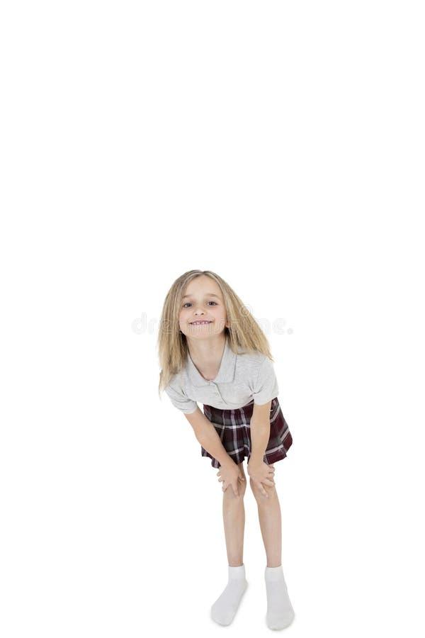 Portret szczęśliwa szkolna dziewczyna zgina nad białym tłem zdjęcie stock