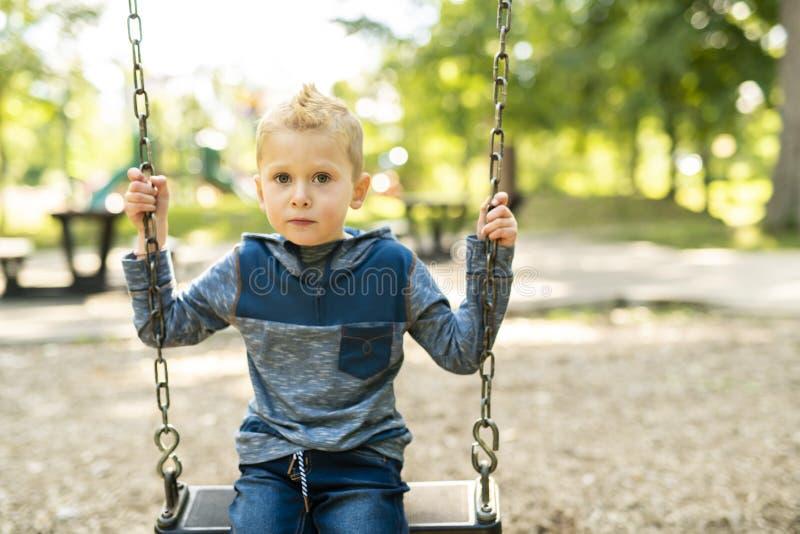 Portret szczęśliwa uśmiechnięta chłopiec na huśtawce zdjęcie stock
