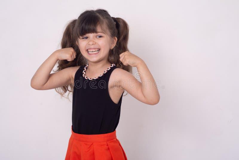 Portret szczęśliwa uśmiechnięta dziewczyna z rękami w górę Elegancka dziecko dziewczyna napina mięśnie zdjęcia stock