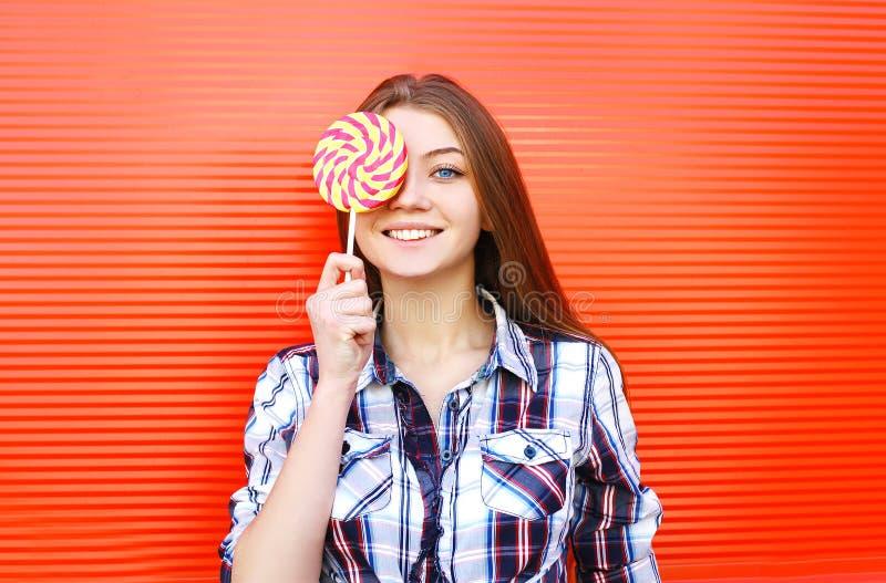 Portret szczęśliwa uśmiechnięta młoda dziewczyna z słodkim karmelu lizakiem ma zabawę zdjęcie stock