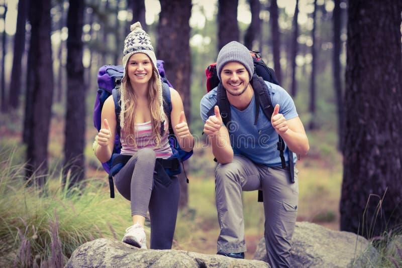 Portret szczęśliwa wycieczkowicz para z aprobatami zdjęcia royalty free