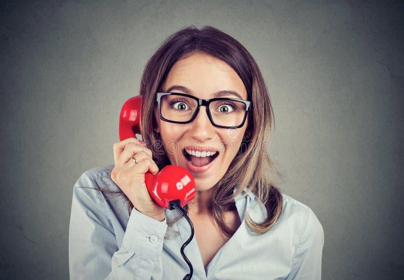 Portret szczęśliwa zadziwiająca kobieta opowiada na czerwonym telefonie zdjęcia stock