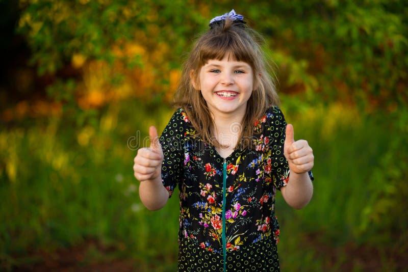 Portret szczęśliwe roześmiane dziewczyny przedstawienia aprobaty w parku obraz royalty free