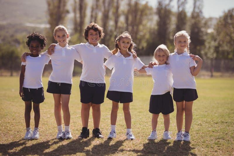 Portret szczęśliwe uczennicy stoi z rękami wokoło w parku fotografia stock