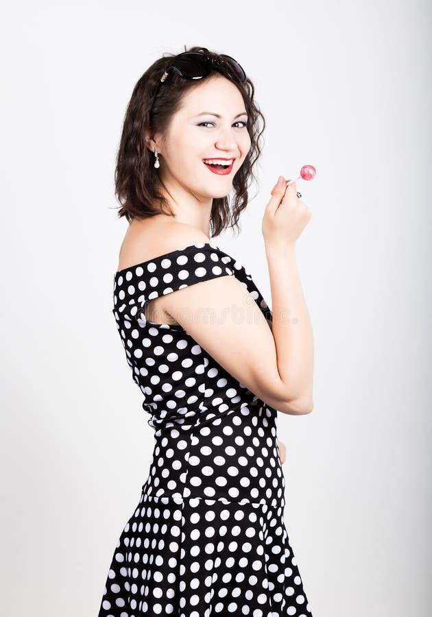 Portret szczęśliwego pięknego młodej kobiety oblizania słodki cukierek i wyrażać różne emocje kierowa ładna kobieta fotografia royalty free