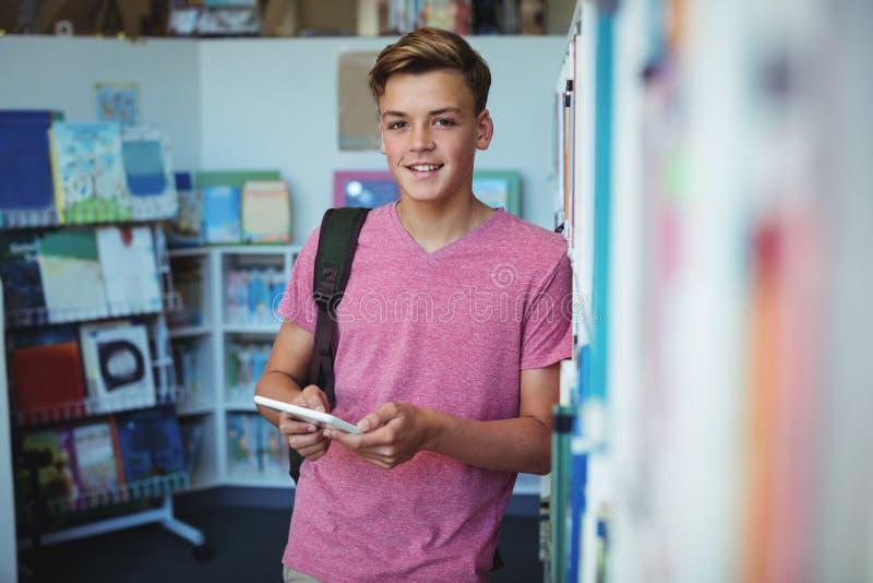 Portret szczęśliwego uczniowskiego mienia cyfrowa pastylka w bibliotece obraz stock
