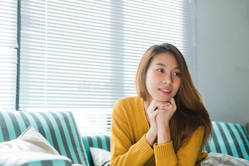 Portret szczęśliwego właściciela domu azjatykcia kobieta uśmiecha się siedzieć na kanapie w żywym pokoju w domowym wnętrzu z perf zdjęcia royalty free