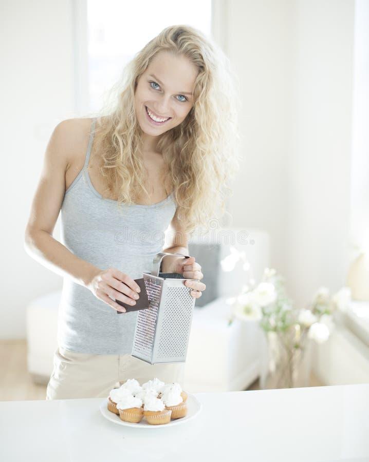 Portret szczęśliwej kobiety drażniąca czekolada na babeczkach przy kontuarem zdjęcia stock