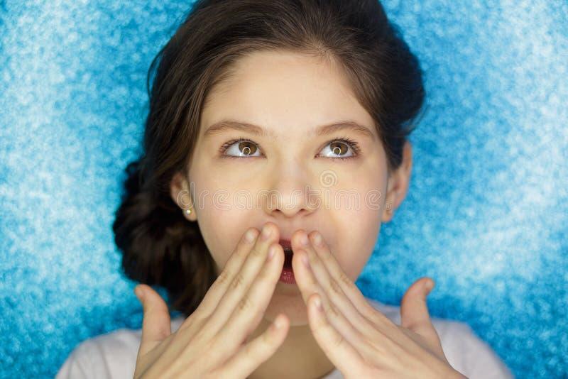 Portret szczęśliwej z podnieceniem dziewczyny otwarty usta utrzymuje ręki odizolowywać nad błękitnym tłem przy ona twarz obrazy royalty free