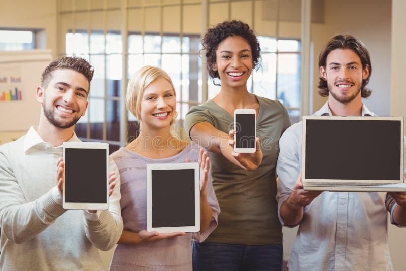 Portret szczęśliwi biznesowi koledzy pokazuje technologie w biurze zdjęcie stock