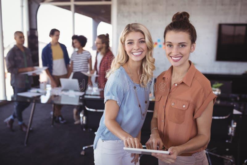 Portret szczęśliwi bizneswomany trzyma cyfrową pastylkę z kreatywnie drużyną obrazy royalty free