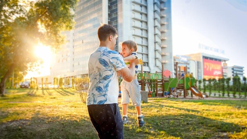 Portret szczęśliwi potomstwa ojcuje przytulenie i przędzalnictwo jego uśmiechnięty mały berbecia syn w parku zdjęcia stock