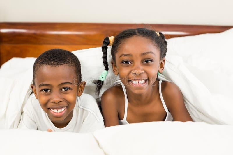 Portret szczęśliwi rodzeństwa pod koc obrazy stock