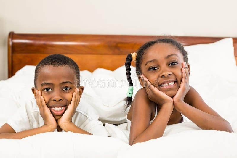 Portret szczęśliwi rodzeństwa w łóżku fotografia royalty free